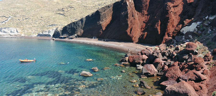 A Praia Vermelha em Santorini, Grécia, tem esse nome devido à coloração de suas rochas